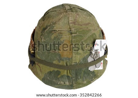 US Army helmet Vietnam war period with camouflage cover and ammo belt, dog tag and amulet - ace of hearts playing card - stock photo