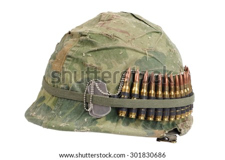 US Army helmet with camouflage cover and ammo belt and dog tags - Vietnam war period - stock photo