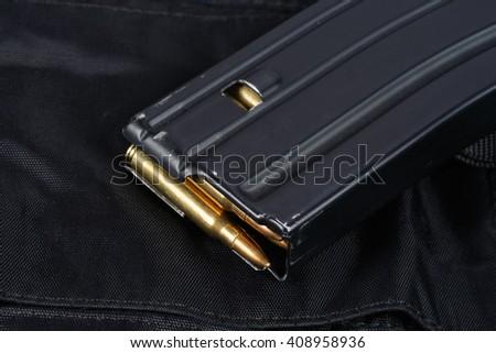 US ARMY M-16 rifle magazine with cartridges on black uniform - stock photo