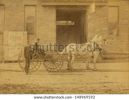 US - Circa 1880 - A vintage photo of three men with a horse drawn wooden wheeled wagon. The wagon is drawn by two white horses and is sitting in front of a building. The street is made of dirt. - stock photo