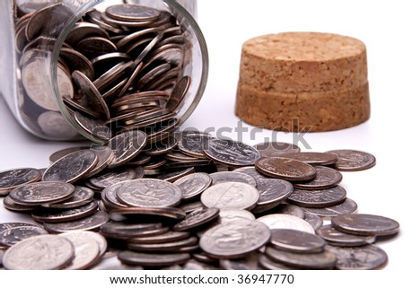 US coins spilling from a coin jar.  Cork stopper in the background. - stock photo