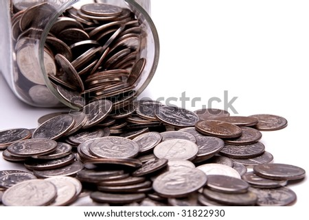 US coins spilling from a money jar. - stock photo