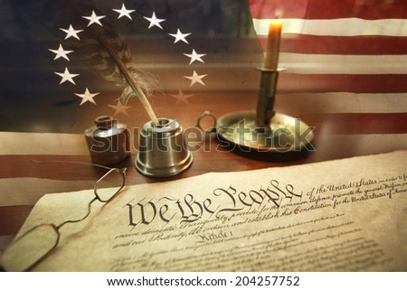 US Constitution with quill pen, ink, glasses, candle and flag with thirteen stars - stock photo