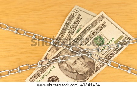 US Currency Under Chains ( Financial Security ) - stock photo