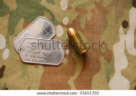 US dog tags and .45 caliber cartridge on multicam background - stock photo