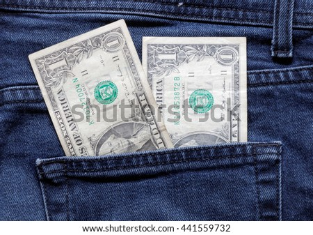 US dollar bank notes sticking up from a jeans pocket