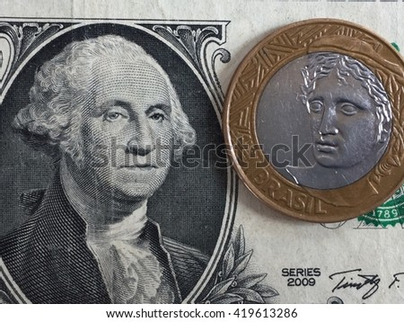 US dollar banknote and Brazilian real coin representing exchange rate