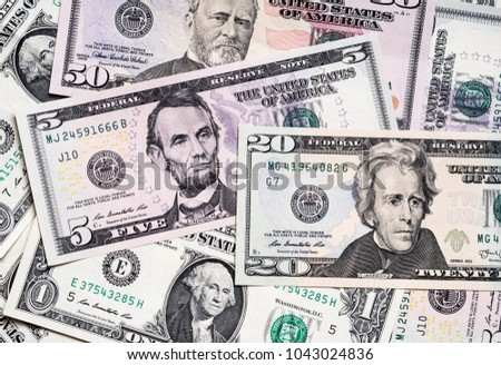 US dollar banknotes scattered on plain surface