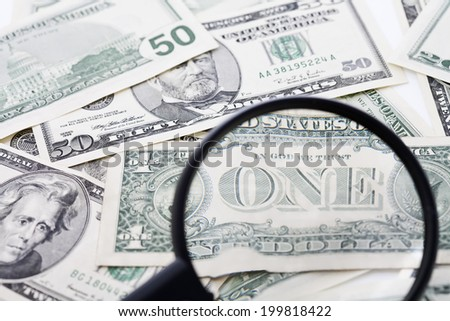 US Dollar bills seen through magnifying glass, close up
