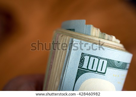 US dollars rolled up in the hand - stock photo