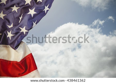 US flag against bright blue sky with clouds