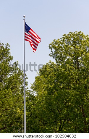 US flag flies on a tall flag pole in a wooded cemetery - stock photo