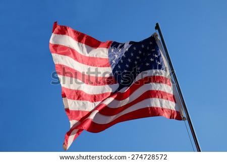 US flag flying in the background of the sky. American symbol of success and freedom. National honor. - stock photo