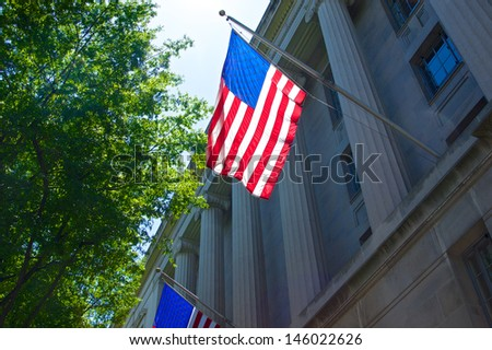 US flag hangs from the columns on the Department of Justice.   - stock photo