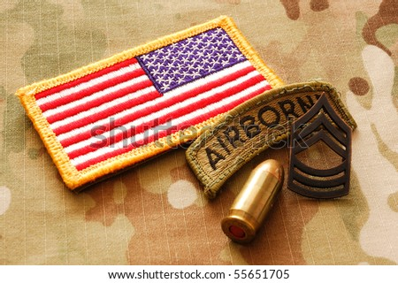 US flag, rank, patch and .45 caliber cartridge on multicam background