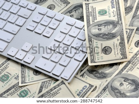 US hundred dollar bills with white modern computer keyboard isolated on white background, selective focus. - stock photo
