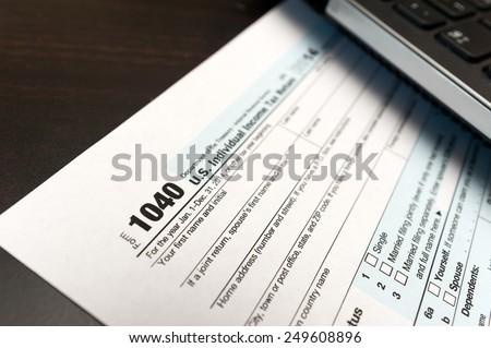US Individual Tax Return Form 1040 close up. selective focus image - stock photo