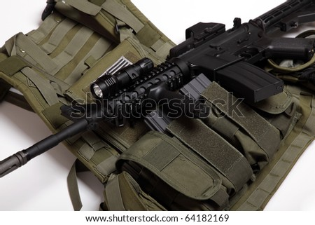 US military concept. Tactical vest and assault rifle close-up. Studio shot. - stock photo