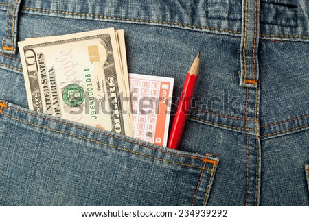 US money and lottery betting slip in back pocket  - stock photo