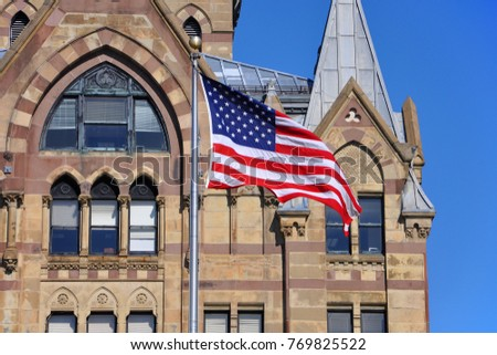 US National Flag in front of Syracuse Savings Bank Building at Clinton Square in downtown Syracuse,  York State, USA.