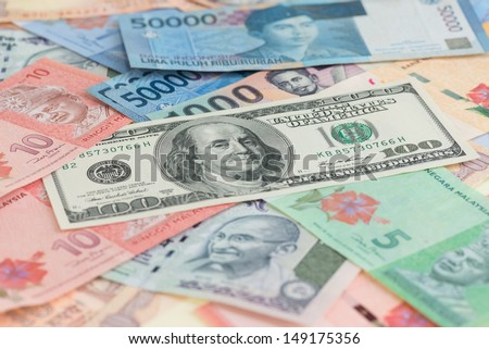 US one hundred dollar bill and Asian currencies background - stock photo