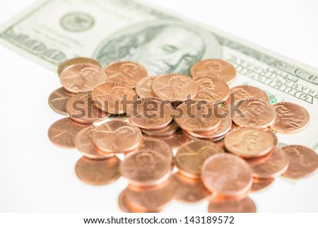 US pennies piled up on one hundred dollar bill close up - stock photo