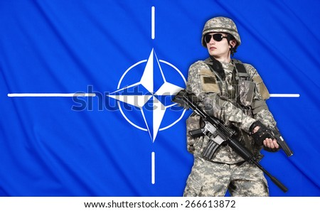 US soldier with gun on a Nato flag background - stock photo