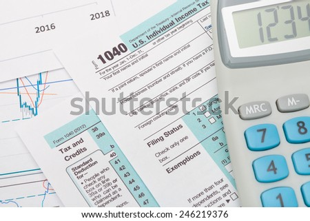 US 1040 Tax Form and calculator over it - stock photo