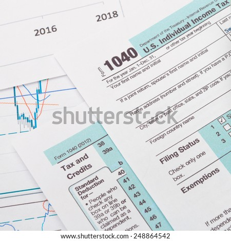 US 1040 Tax Form and calculator over it - studio shot - stock photo