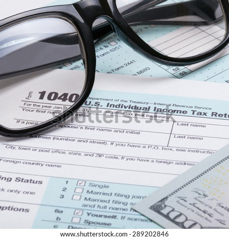 US 1040 Tax Form, glasses and dollars - close up studio shot - stock photo