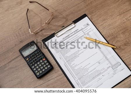 US 1120 tax form, pen, calclator on desk - stock photo
