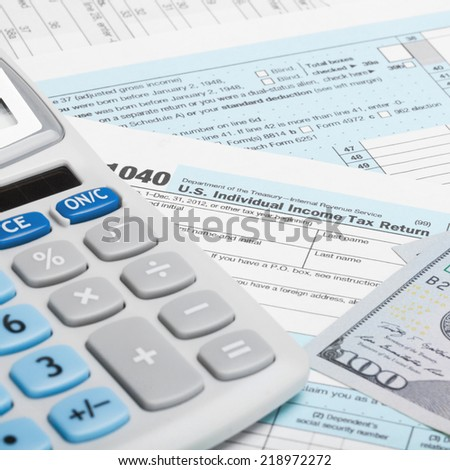 US Tax Form 1040 with calculator and US dollars - 1 to 1 ratio - stock photo