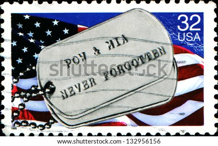 "USA - CIRCA 1995: A stamp printed in United States of America shows US Flag and military Badge, with the inscription ""Prisoners of War & Missing in Action never forgotten"", circa 1995 - stock photo"