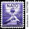 USA - CIRCA 1952: A stamp printed in USA shows the Torch of Liberty and Globe, devoted to 3rd anniv. of the signing of the North Atlantic Treaty, circa 1952 - stock photo