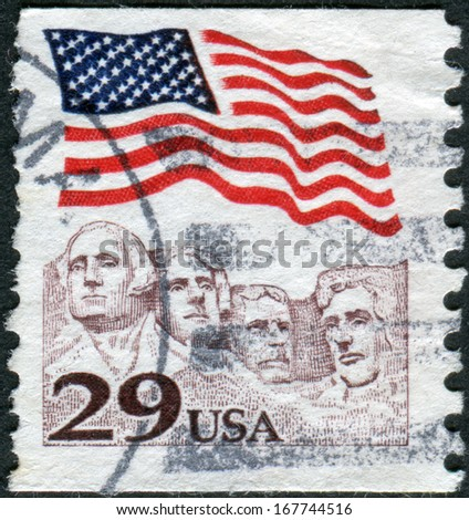 USA - CIRCA 1991: Postage stamp printed in the USA, shows the national flag over Mount Rushmore National Memorial, circa 1991 - stock photo