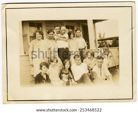 USA - CIRCA 1930s: Reproduction of an antique photo shows large farming family for several generations, posing against the backdrop of the rural house - stock photo