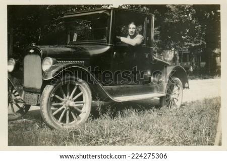 USA- CIRCA 1920s: Vintage photo shows the man behind the wheel of a car.   - stock photo