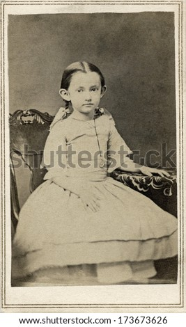 USA - CONNECTICUT - CIRCA 1863 A vintage Cartes de visite photo of a young girl sitting in a chair and wearing a dress with pig tails in her hair. A photo from the Civil War Victorian era. CIRCA 1863