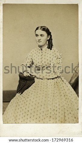 USA - CONNECTICUT - CIRCA 1867 - A vintage Cartes de visite photo of young girl sitting in chair with ringlets in hair. She is dressed in hoop skirt dress. Photo from the Victorian era. CIRCA 1867 - stock photo