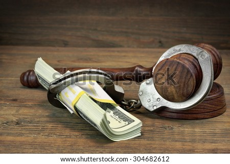 USA Dollar Money Cash, Real Handcuffs And Judge Gavel On Rough Wood Background. Concept For Arrest, Corruption, Bail, Crime, Bribing or Fraud. - stock photo