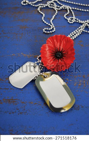 USA Memorial Day concept of red remembrance poppy on dark blue vintage distressed wood table, with soldiers dog tags.  - stock photo