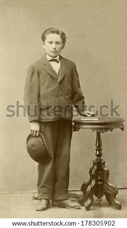 USA - MINNESOTA - CIRCA 1870 - A vintage Cartes de visite photo of a young boy standing next to a round table. He is wearing a suit, tie and derby style hat. A photo from the Victorian era. CIRCA 1870 - stock photo
