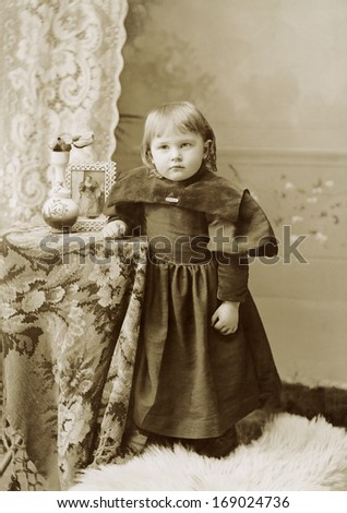 USA - NEW YORK - CIRCA 1895 - A vintage antique photo of a two year old little girl dressed in a Victorian style dress. She is standing next to a table. A photo from the Victorian era. CIRCA 1895 - stock photo