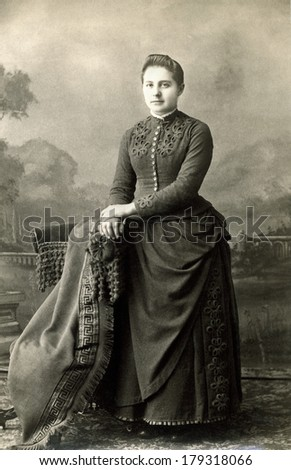 USA - NEW YORK - CIRCA 1885 A vintage cabinet card of a young woman dressed in a Victorian style bustle dress standing with her hands placed on a chair. Photo is from the Victorian era. CIRCA 1885 - stock photo
