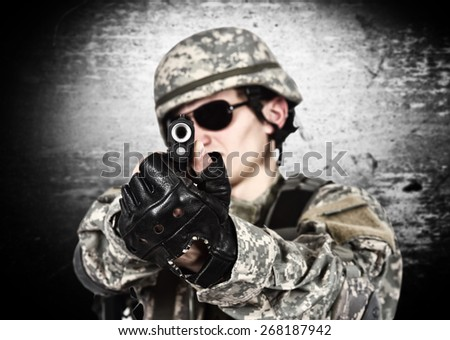 USA soldier aiming a gun  on gray background - stock photo