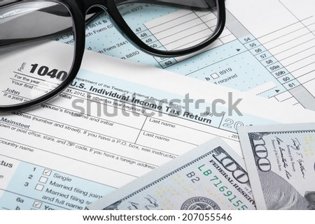 USA Tax Form 1040 with glasses and 100 US dollar bills - stock photo