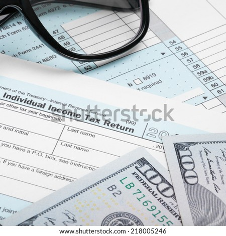 USA Tax Form 1040 with glasses and 100 US dollar bills - 1 to 1 ratio - stock photo