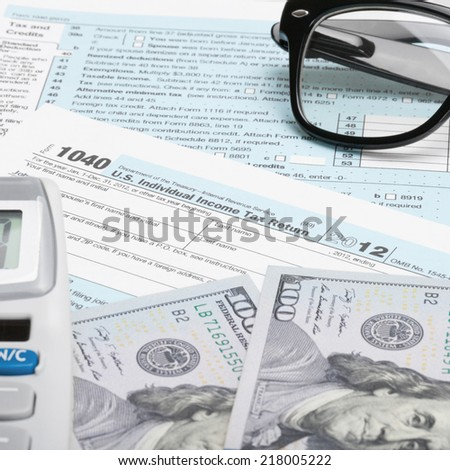 USA Tax Form 1040 with glasses, calculator and 100 US dollar bills - 1 to 1 ratio - stock photo