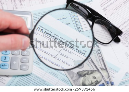 USA 1040 Tax Form 1040 with magnifying glass, glasses, dollars and calculator over it - stock photo