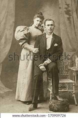 USA - TEXAS - CIRCA 1895 - A vintage photo of a young couple. The husband is sitting and the wife is standing. She is dressed in a Victorian style dress. A photo from the Victorian era. CIRCA 1895 - stock photo